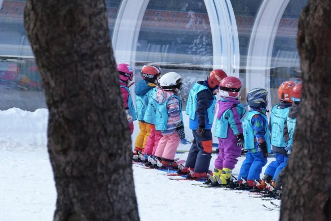 Los niños en el jardín de nieve de espaldas todos equipados para esquiar.