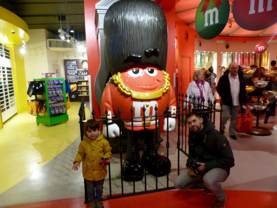 Eric y Alex posando al lado del M&M rojo disfrazado de bobby